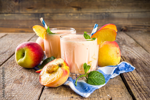 Obraz Summer breakfast drink, fresh blended peach smoothie, peach yogurt with nectarine fruit slices, rustic wooden background copy space - fototapety do salonu