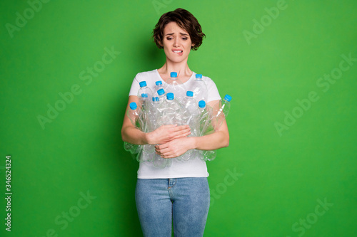 Fototapeta Photo of beautiful lady hold plastic bottles carry trash recycling service irresponsible people human beings biting lips confused wear white t-shirt jeans isolated green color background obraz