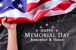 Happy Memorial Day. Man's hand hold American flags with the text REMEMBER & HONOR against a blackboard background. May 25.