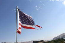 Low Angle View Of Torn American Flag Against Blue Sky