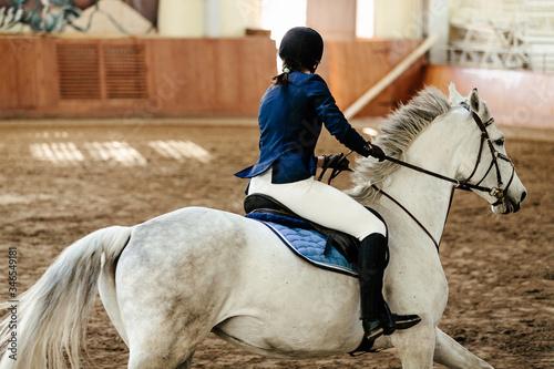 Obraz na plátně close up horsewoman a horse riding indoors arena