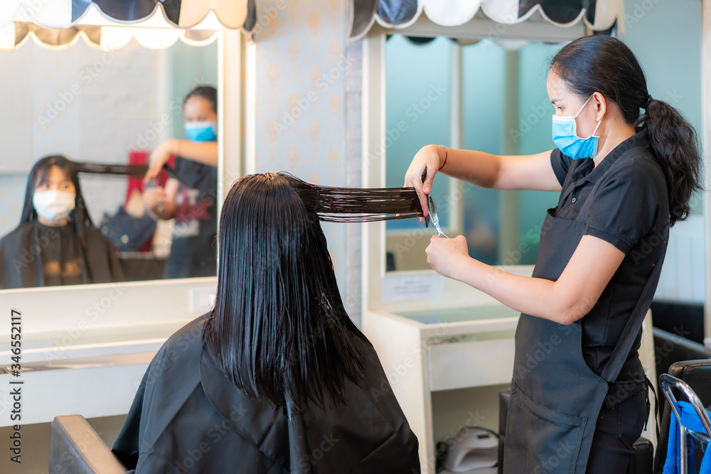 Fototapeta Asian young woman wearing face masks to protect themselves from Covid-19 during hairdresser trimming black hair with scissors in beauty salon.