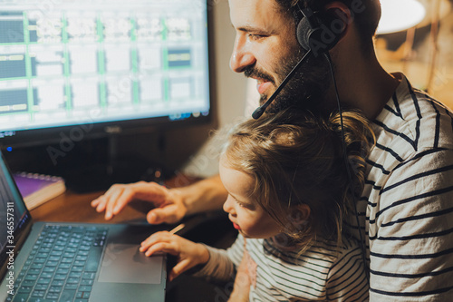 Photo Stylish Bearded father working at home while babysitting his playful daughter