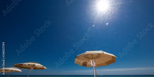 Fototapeta ombrelloni aperti e sullo sfondo mare  e cielo  blu e un motoscafo pronto a partire obraz