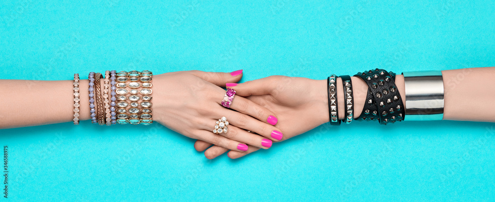 Fototapeta Fashion. Female hand, Stylish jewelry. Minimal design. Summer hipster woman luxury accessories, bracelets ring. Creative art friendship concept Trendy jewelry on blue, banner