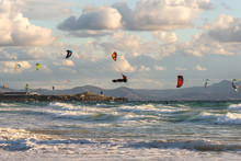 Kitesurfing In Tarifa. Plenty Of Colorful Kites Flying Against A Background Of The Mountains, Beautiful Clouds And Waves Of The Atlantic Ocean