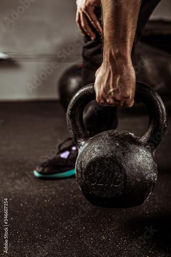 Obraz Dłonie trzymające kettlebell, sportowiec uprawiający crossfit, podnoszenie ciężarów. - fototapety do salonu