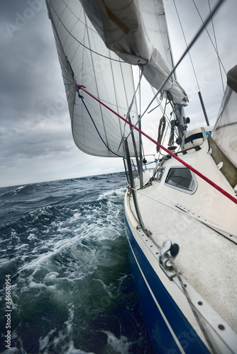 Fototapety, obrazy: Yacht sailing in a thunderstorm on a rainy day. Close-up view from the deck to the bow, mast and sails. Dramatic stormy sky, dark clouds. Waves and water splashes. Rough weather. Baltic sea, Sweden