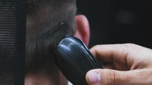 CU, Slow Motion: Skilled Barber Does Haircut To Male Client Shaving Black Hair On Head Back With Clipper Machine In Barbershop Backside Close View