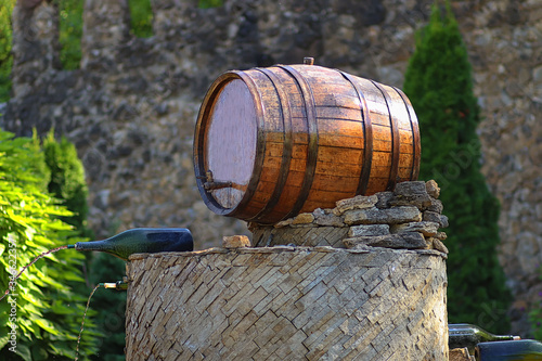 Photo Wine barrel and wine bottles that pour out of them