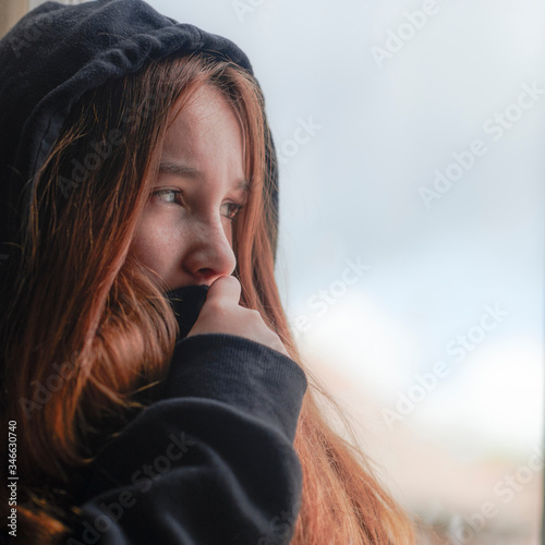 Photo Scared teenage girl having abuse problems looking out window