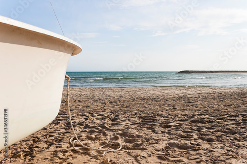 Bow of a white boat aground on Cubelles beach in the Mediterranean Sea in a sunny day of summer Canvas Print