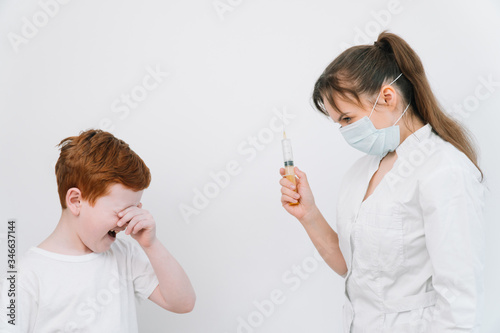 Photo Little boy is afraid of the doctor with a syringe