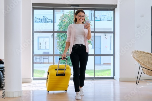 Woman tourist hotel guest with suitcase in lobby of hotel using smartphone Wallpaper Mural