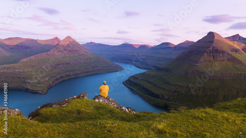 Fototapeta Lonely tourist in yellow jacket looking over majestic fjords of Funningur, Eysturoy island, Faroe Islands. Landscape photography obraz