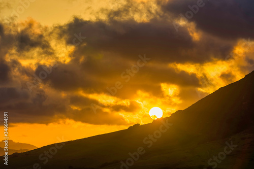 Sun setting at Sunset behind Mountainside, Clouds