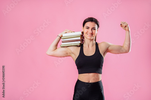 Fototapeta Beautiful, attractive, muscular girl holding heavy set of books on one hand, and with her second hand showing her large muscles
