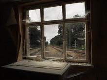 Railroad Tracks Seen Through Broken Glass Window