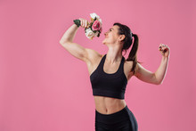 Attractive Girl With A Muscular And Very Beautiful Body Holding In Hand Bouquet Of Pink Peonies Flowers. Using Flowers Instead Of Kettlebells. With One Hand Shows Pumped Up Biceps And Smelling Flowers