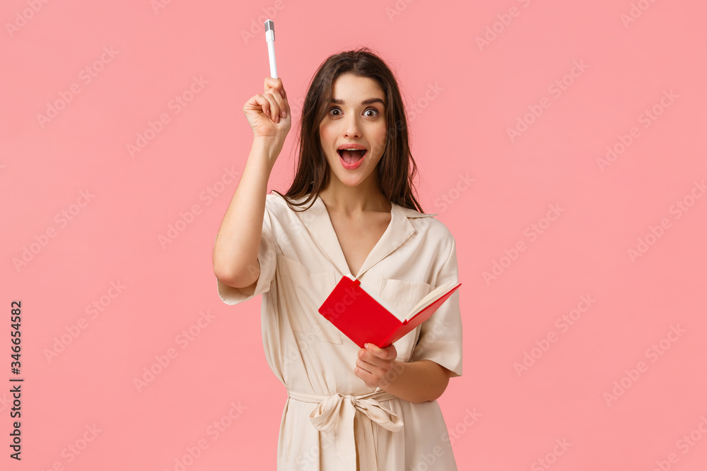 Fototapeta Girl got inspired and have perfect idea, saying yes and raising pen writing, creating something, solving exercises for english classes, standing in dress holding red cute notebook, pink background