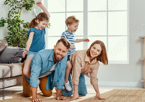 Photo Happy parents giving piggyback ride to kids at home.