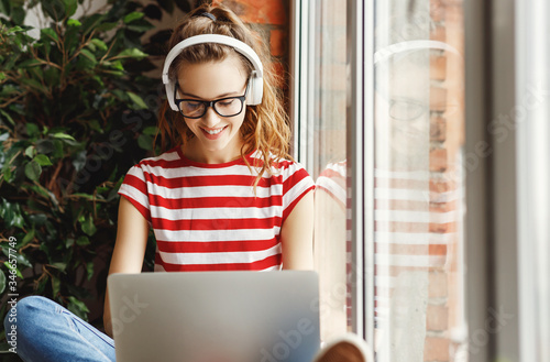 Fototapeta Happy young woman in headphones listening to music and working on laptop at home obraz
