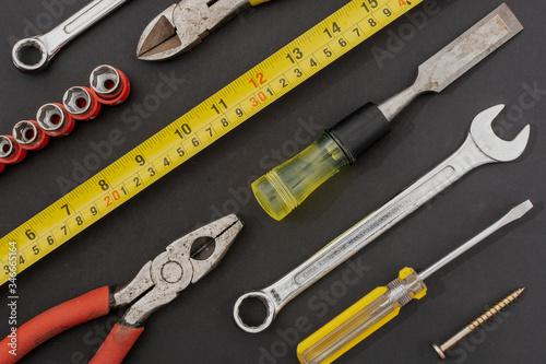 Grupo de herramientas acomodados sobre una superficie de color negro Wallpaper Mural