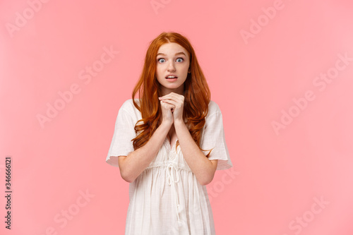 Photo Hopeful and amused, redhead female in white dress, holding hands together over c