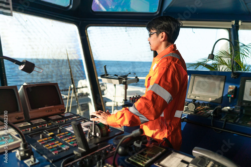 Photo Filipino deck Officer on bridge of vessel or ship wearing coverall during navigaton watch at sea