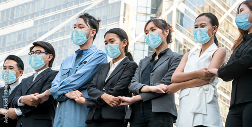 Fototapety, obrazy: Confident business people with face mask protect from Coronavirus or COVID-19. Concept of help, support and collaboration together to overcome epidemic of Coronavirus or COVID-19 to reopen business.