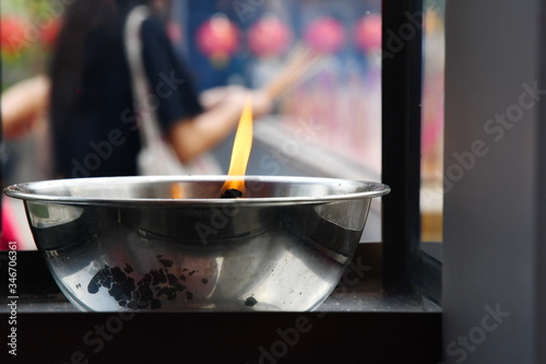 Photo Flame candles in sacred censer that people use to light joss sticks or candles to respect sacred objects