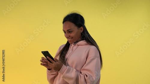 Pretty black woman finding something incredible surfing the Internet on smartphone Tapéta, Fotótapéta