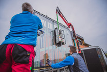 Two Male Workers Lifting A Big Glass Window Or Piece Of Glass From A Lorry Or Truck Using A Hydraulic Jack Or Hydraulic Arm In Front Of A New House Being Built.