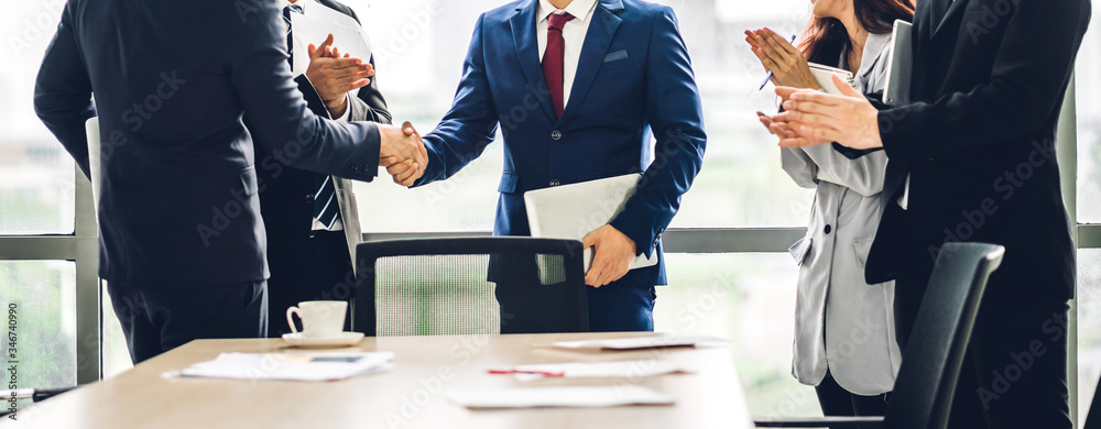 Fototapeta Image two business partners in elegant suit successful handshake together in front of group of casual business clapping hands in modern office.Partnership approval and thanks gesture concept