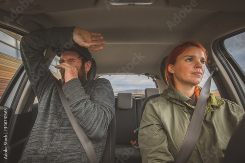 фотографія A woman is calmly driving a car and a man in the next seat is scared as hell