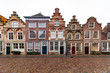 canvas print picture - Amsterdam city house with the typical Flemish architectural style laying in line under a tiny rain wetting the brick pavement street