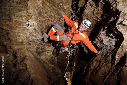 Speleologist descend by the rope in the deep vertical cave tunnel Wallpaper Mural