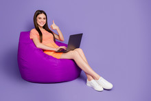 Full Body Profile Photo Of Nice Lady Sitting Comfy Beanbag Browsing Notebook Raise Thumb Finger Up Wear Orange Striped T-shirt Jeans Mini Skirt Isolated Pastel Purple Color Background