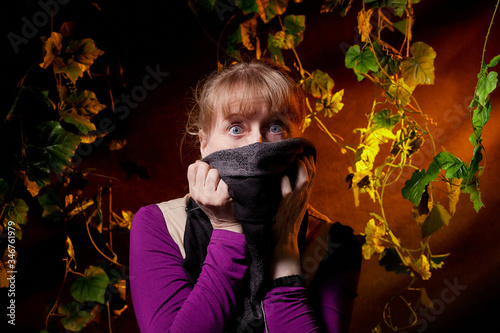 A girl in a dark room among Liana plants with green leaves and a black background Wallpaper Mural