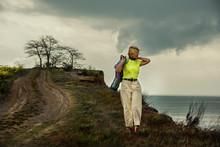 A Woman Walking Along A Dirt ...