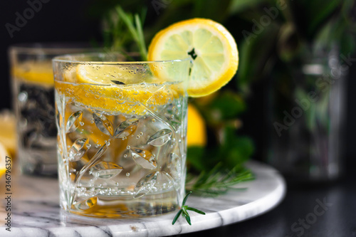 Photo Lemonade, lemon mojito cocktail, cold, iced,refreshing summer drink in glasses with slices of lemon on marble tray