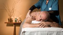 Uomo Anziano In Completo Relax Si Fa Massaggiare Su Un Lettino Da Una Massaggiatrice Professionista In Un Centro Massaggi