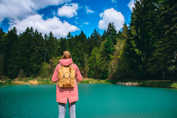 Female hiker in beautiful nature. Woman standing by Turquoise lake. Green trees and blue sky in background. Edit space. Banska Stiavnica, Slovakia