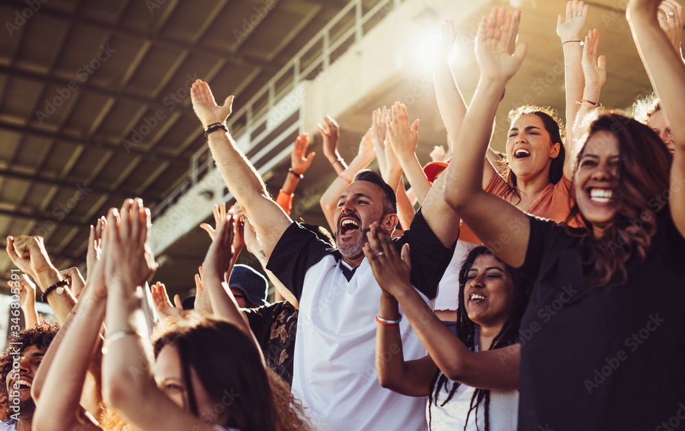 Fototapeta Crowd of sports fans cheering during a match in stadium