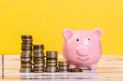 Fototapeta pink piggy bank on a yellow background, space for text. Finance, saving money, crisis. Business or Retirement Savings obraz