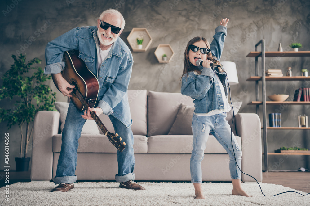 Fototapeta Photo of two people funky grandpa play guitar small nice granddaughter mic singing cool style sun specs denim clothes repetition school concert stay home quarantine living room indoors