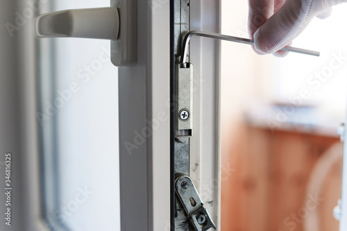 Photo The man makes the adjustment of the pvc door mechanism with an allen key