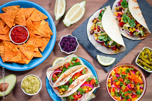 Obraz na plátně Table with tacos, mango salsa, nachos with sauce, guacamole, lemon beer