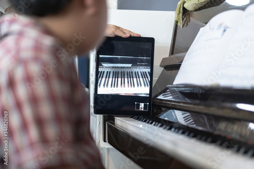 Fototapeta A boy is learning piano online with a tablet by the social network . obraz