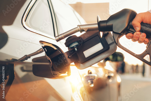 Photographie Gas pump nozzle in a hand refuelling a car at gas tank